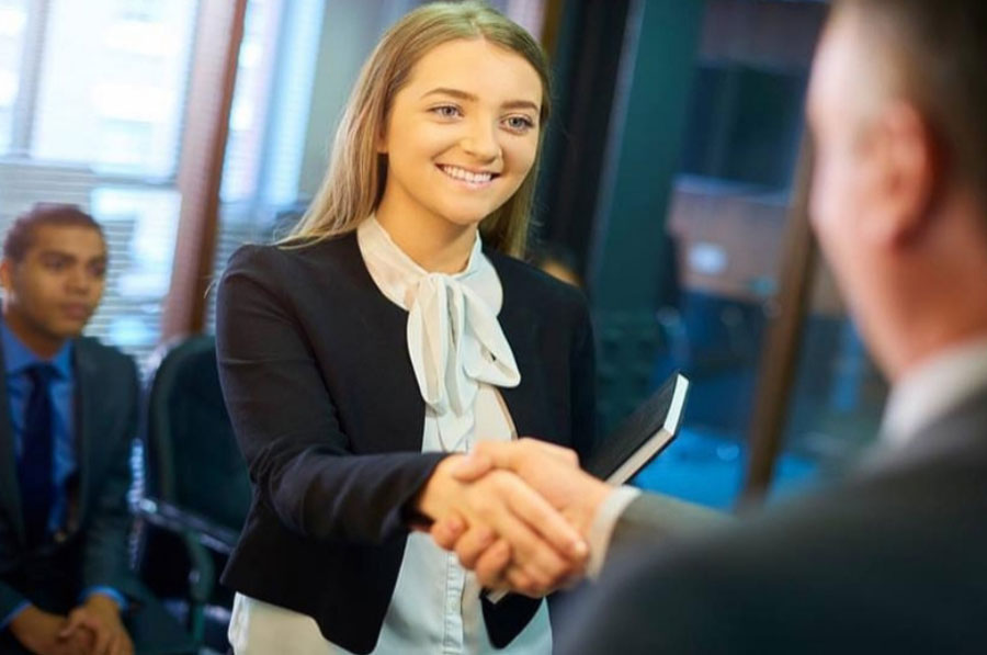 An interviewer shaking hands with a job candidate