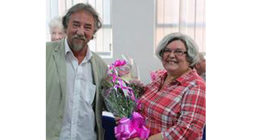 Kevin Hogan presents Barbara Hodson with flowers on her retirement from the University.
