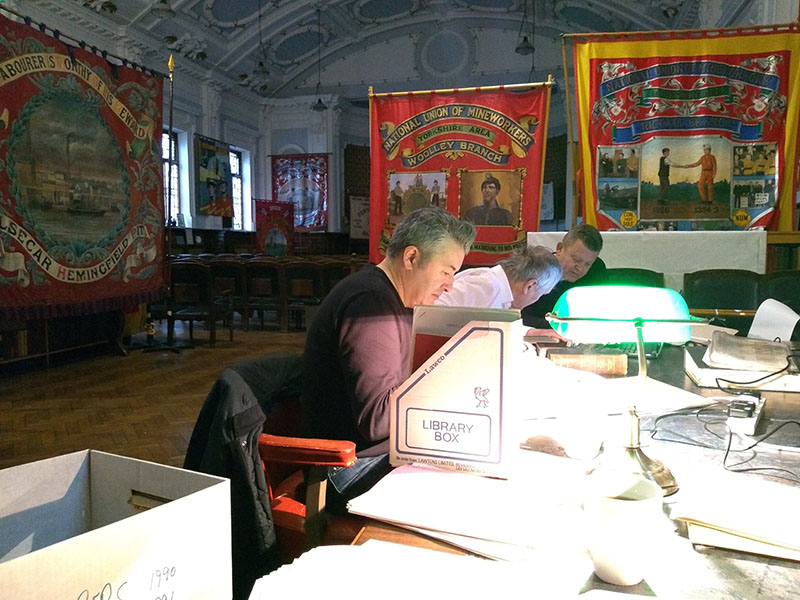 Researchers working in the NUM great all with papers in the foreground and banners in the background